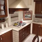 Cucina in muratura completa di elettrodomestici e tavolo e sedie